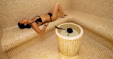 Jeune femme se prélassant dans un hammam paré de mosaïques